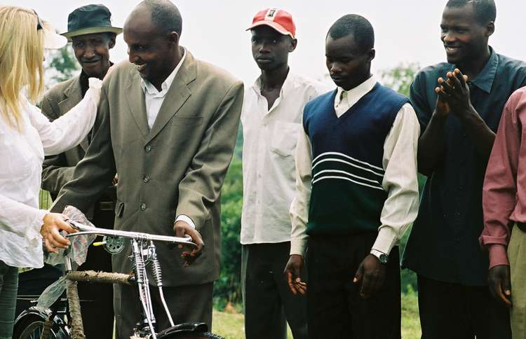 Shelene presents donated bikes to a group of Ugandan pastors.
