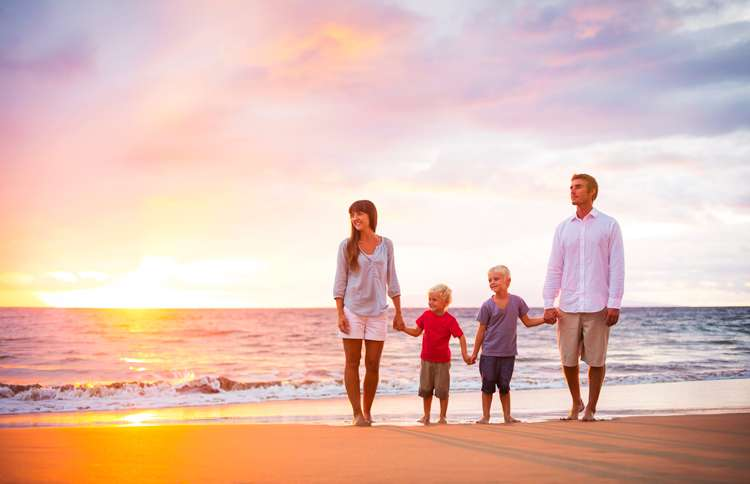 A family of four strolls the beach as the summer sun sets on the horizon.