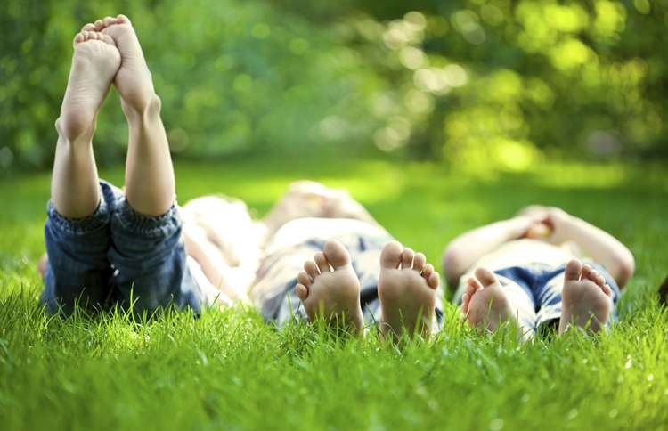 Barefoot children lie on their backs in the grass on warm, sunny summer day.