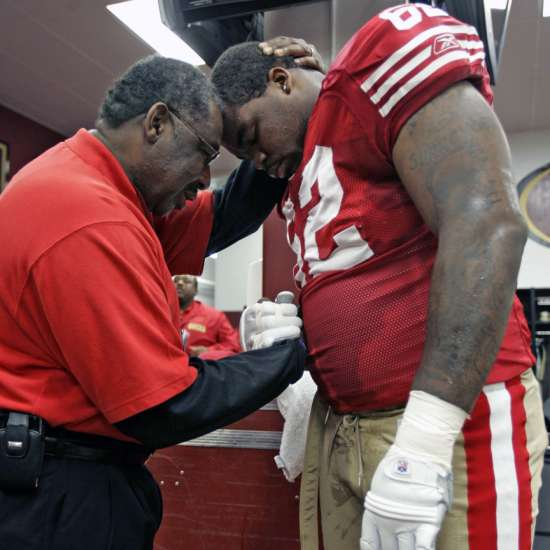 Smith ministers to Chilo Rachal in the locker room before a 2008 home game against the Washington Redskins.