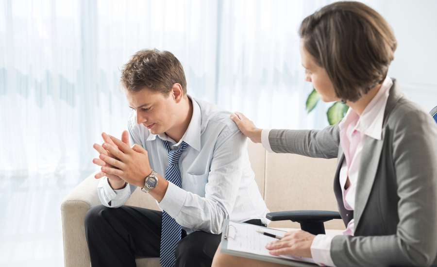 A female therapist comforts her male client in a session