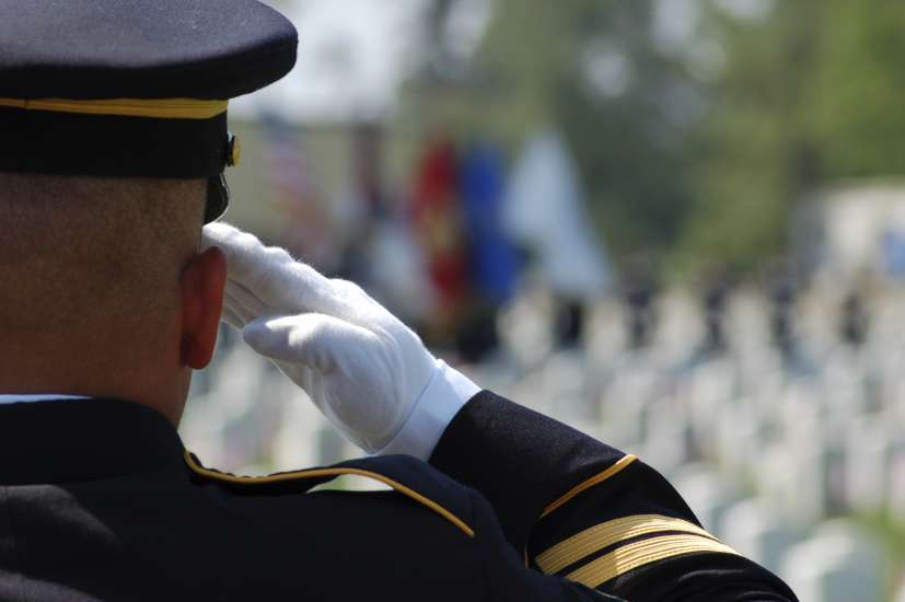 Soldier saluting fallen soldiers in a cemetary on Memorial Day