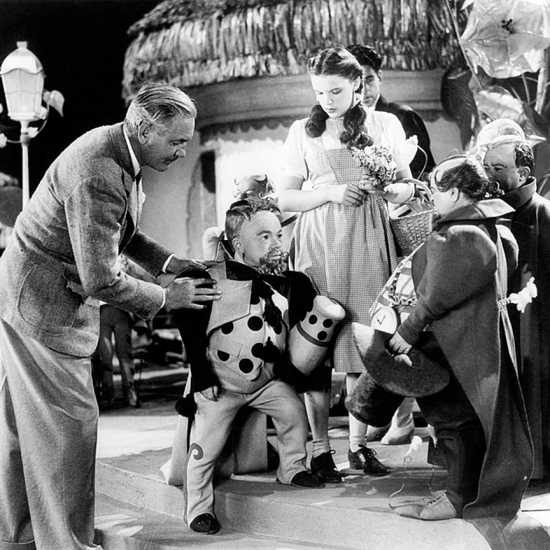 Victor Fleming (left) works with Judy Garland and some of the actors who played the Munchkins