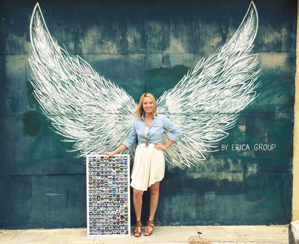 A young woman poses in front of a pair of Erica Group's painted wings