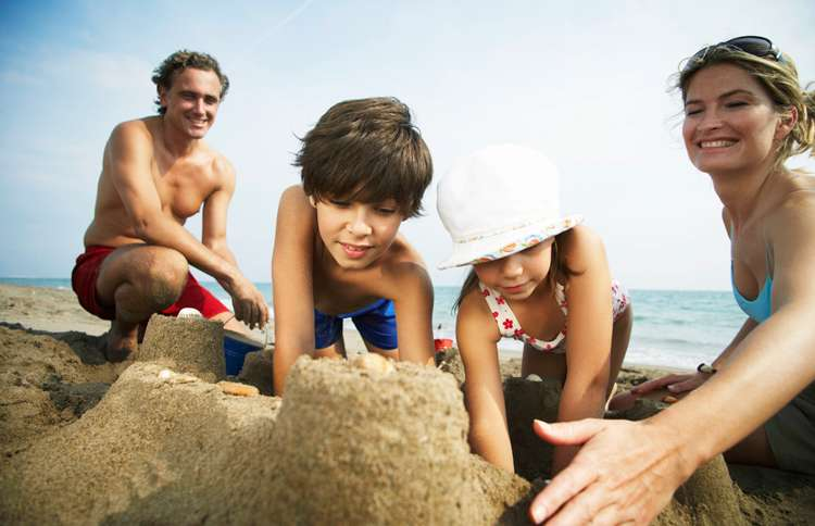 A happy family builds sand castles at the beach.