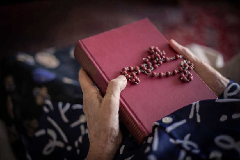 Hands clutching a bible and rosary