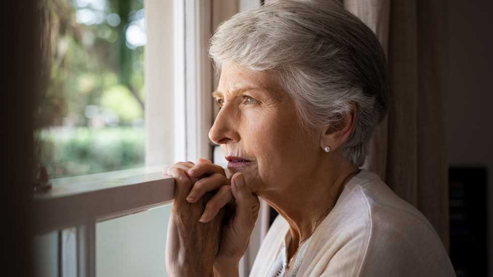 A senior woman looking contemplative out of a window.