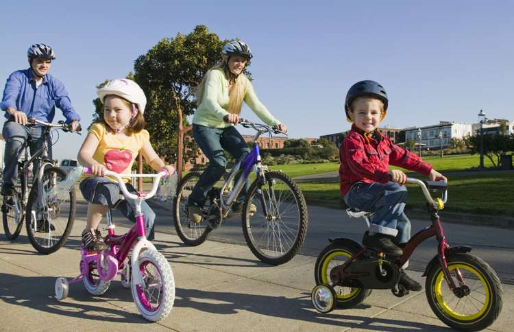 A smiling family of four takes a bike tour of their hometown.