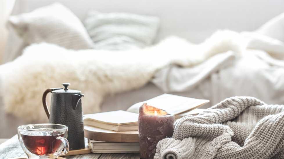 Home comfort with blankets, tea and a candle.