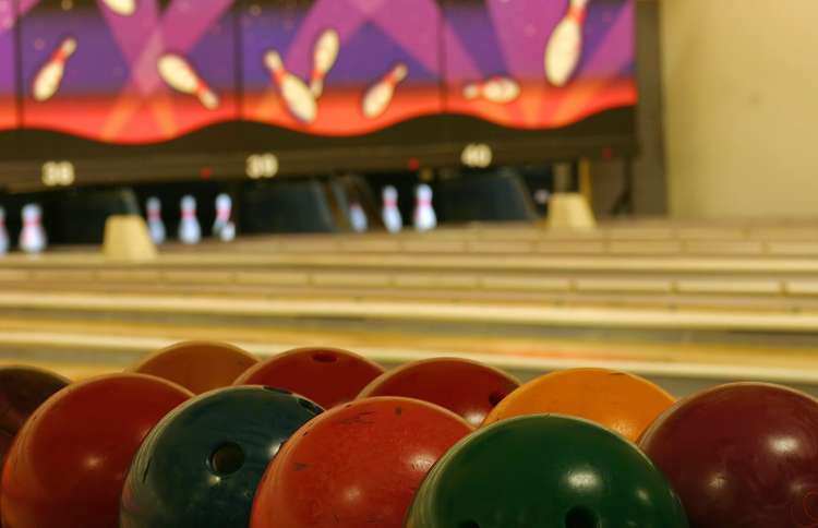 bowling balls lined up on a rack at bowling alley with lanes and pins in the background