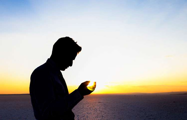 Man standing in front of the horizon praying