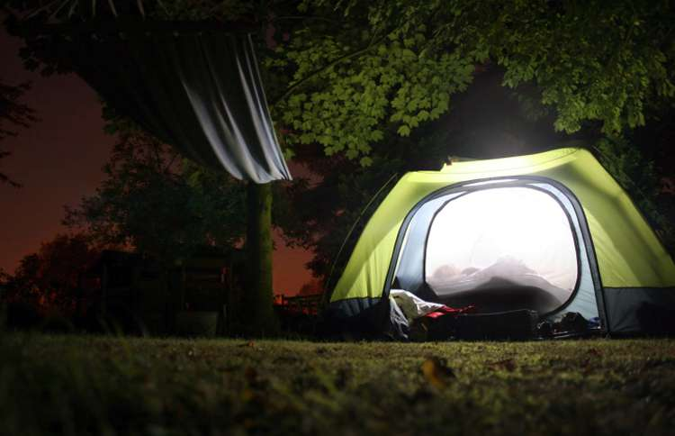 A family enjoys time together in a glowing tent in the back yard