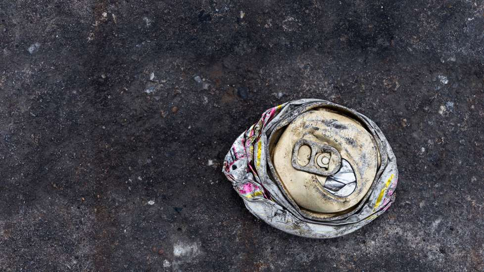 An old, crushed soda can by the side of the road