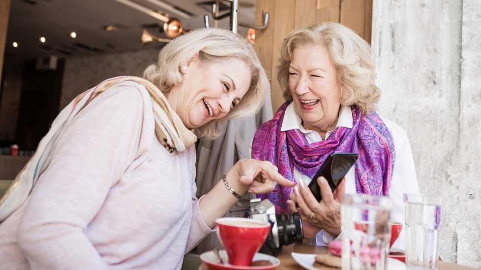 Two woman laughing over coffee