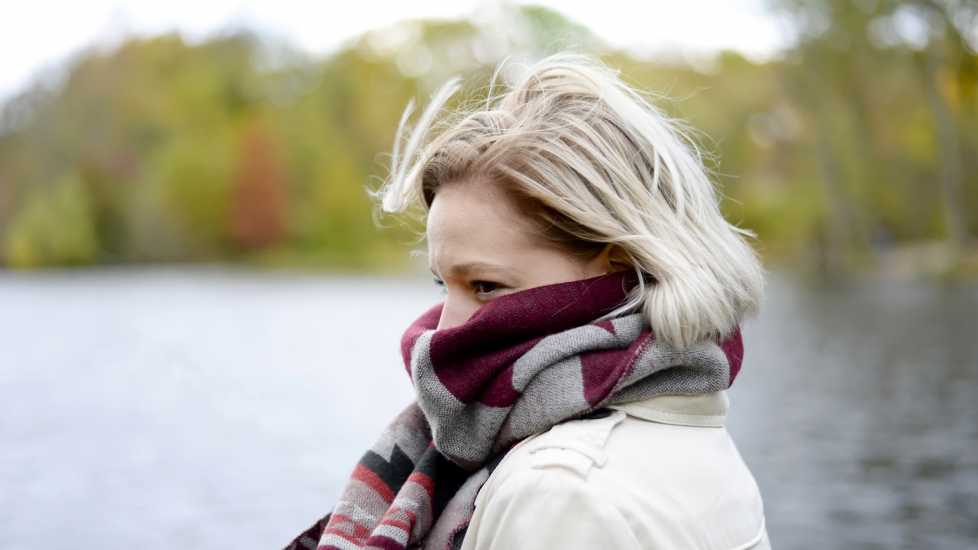 Health myths about Winter: Cold Air Makes You Sick. Woman bundled up with scarf outside. better living health wellness