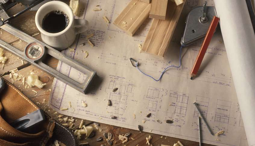 An assortment of construction tools surrounded by sawdust