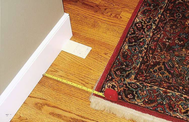 A white card marks the where the left edge of the rug was the night before this picture was taken. The rug has moved several inches.
