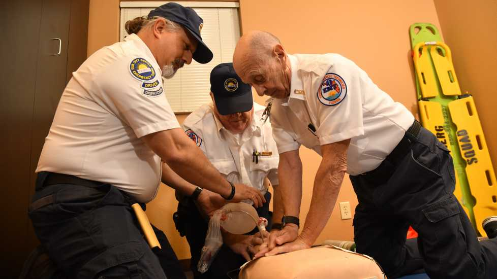 Captain Robert Leonard leading a team in a CPR drill. The EMR, EMT, and ambulance driver all have roles providing lifesaving CPR to a patient.