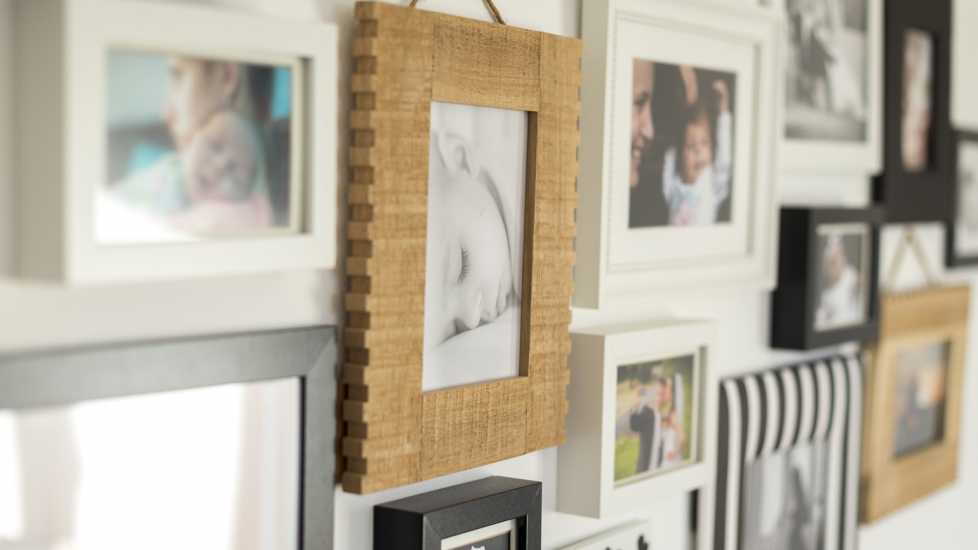 A white wall with photos of the family in various photo frames.