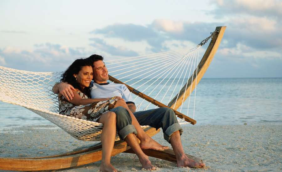 a man and a woman cuddle on a hammock on the beach on a nice day