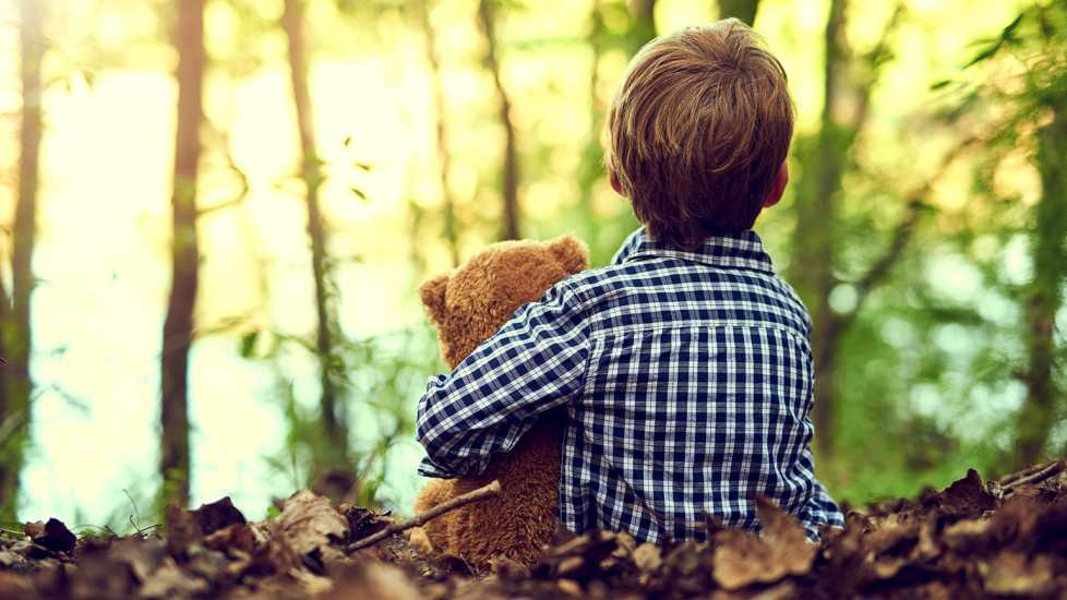 A young boy with a teddy bear sitting outside in a forest.