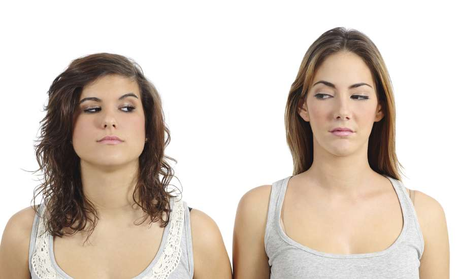 two women stare at each other as if they are suspicious of the other