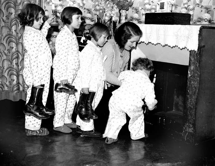 A mother helps her children place their shoes by the fireplace on Christmas Eve