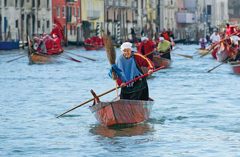 A man dressed as La Befana partcipates in the holiday boat race on Venice's Grand Canal