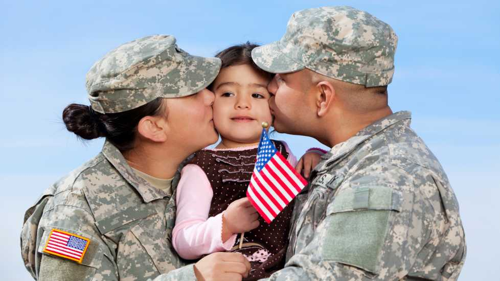 Military couple hugging child