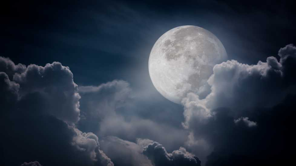 A full moon at night with clouds surrounding.
