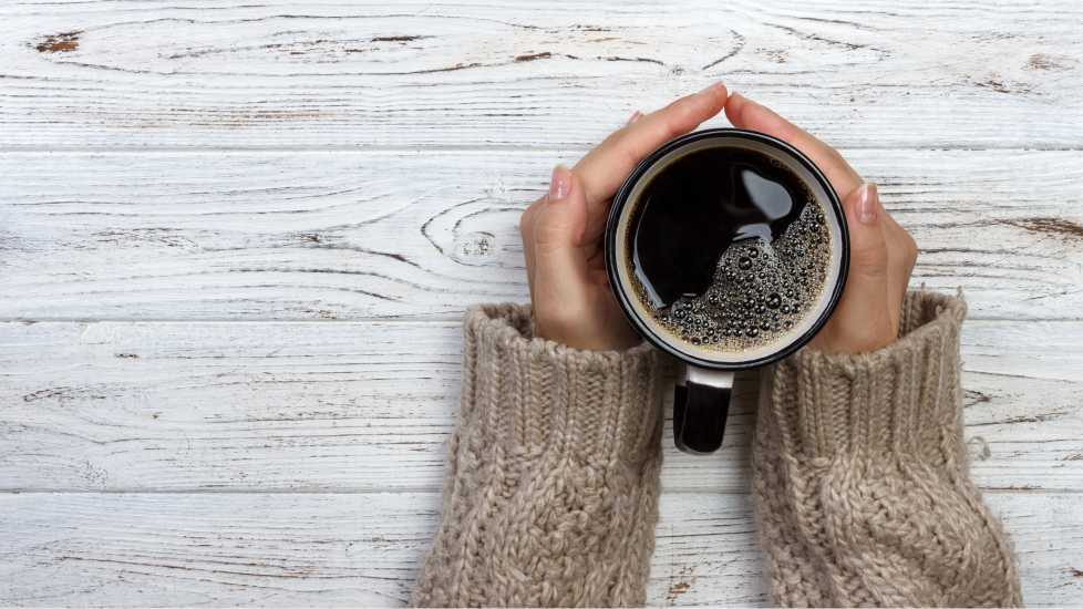 Hands grasping a cup of coffee