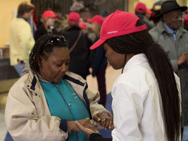 OurPrayer Manager, Ty'Ann Brown prays with another during an OurPrayer Event.