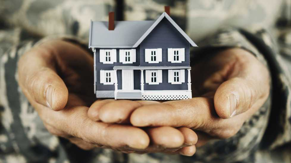 Military member holding miniature house