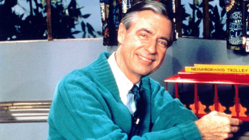 A smiling Fred Rogers sitting near the red toy neighborhood trolley.