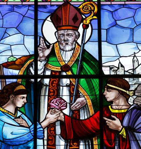 Guideposts: St. Valentine performs the wedding of a young couple who are clasping a rose, as depicted in stained glass in the Basilica of St. Valentine in Terni, Italy