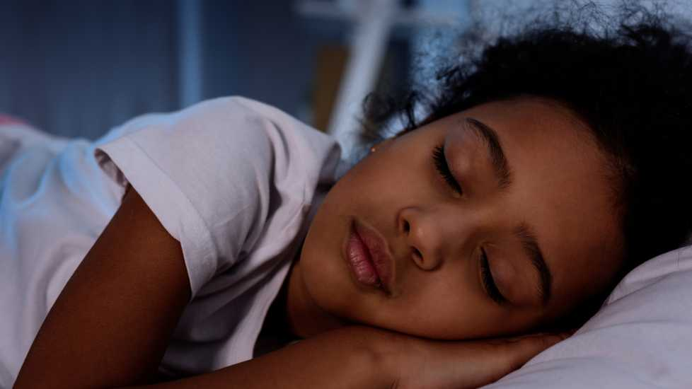 A close-up of a young girl sleeping.