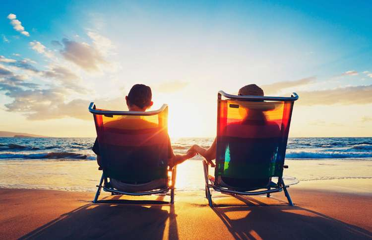 Guideposts: An older couple clasps hands while seated in beach chairs at the seashore