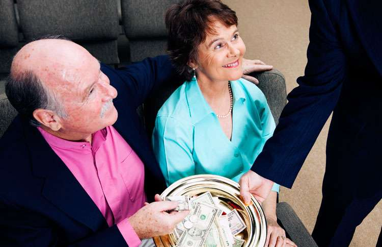 A smiling married couple places a donation in a church offering plate
