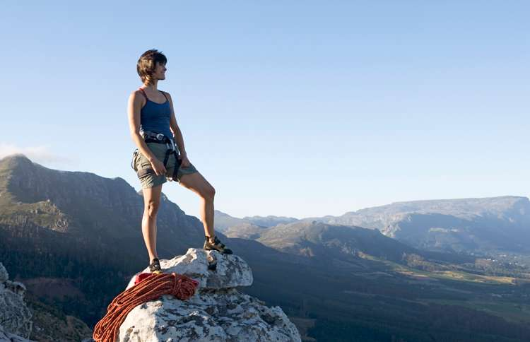 Guideposts: A woman stand atop a mountain's peak, gazing out at the world below