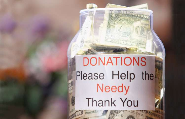 A charity donation container overflows on a retail establishment's counter