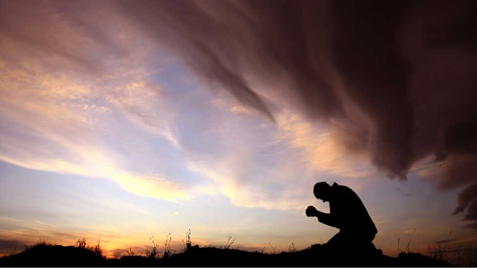 A silhouette of a man praying outdoors against a colorful sunset.