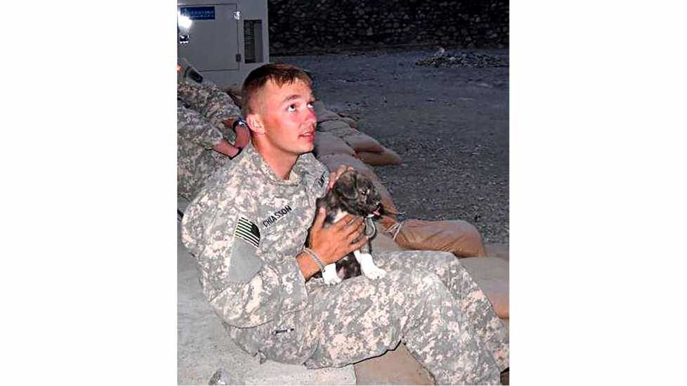 Chris in fatigues with Bear as a puppy.