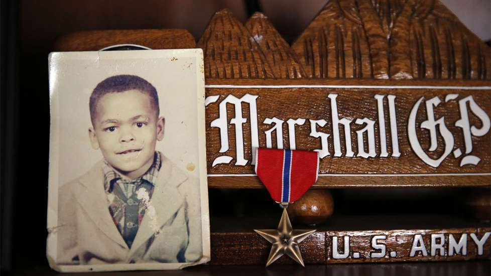 A childhood photo of Sgt. Powell rests alongside the Bronze Star he earned in Iraq at his home in Crescent, Oklahoma.