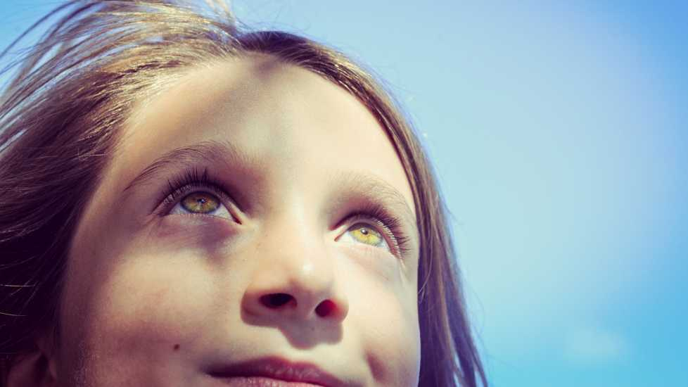 A close up of a young girl looking up at the sky.
