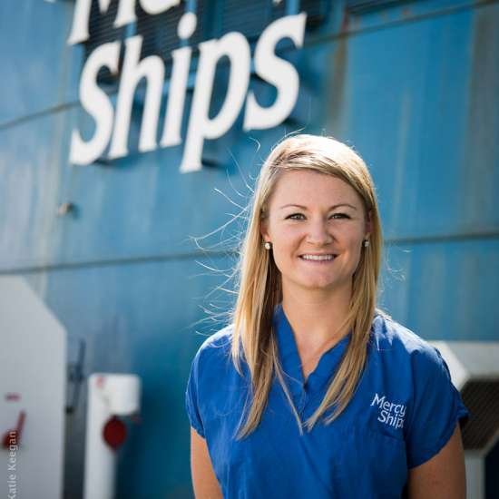 Heather poses in front of a Mercy Ships vessel