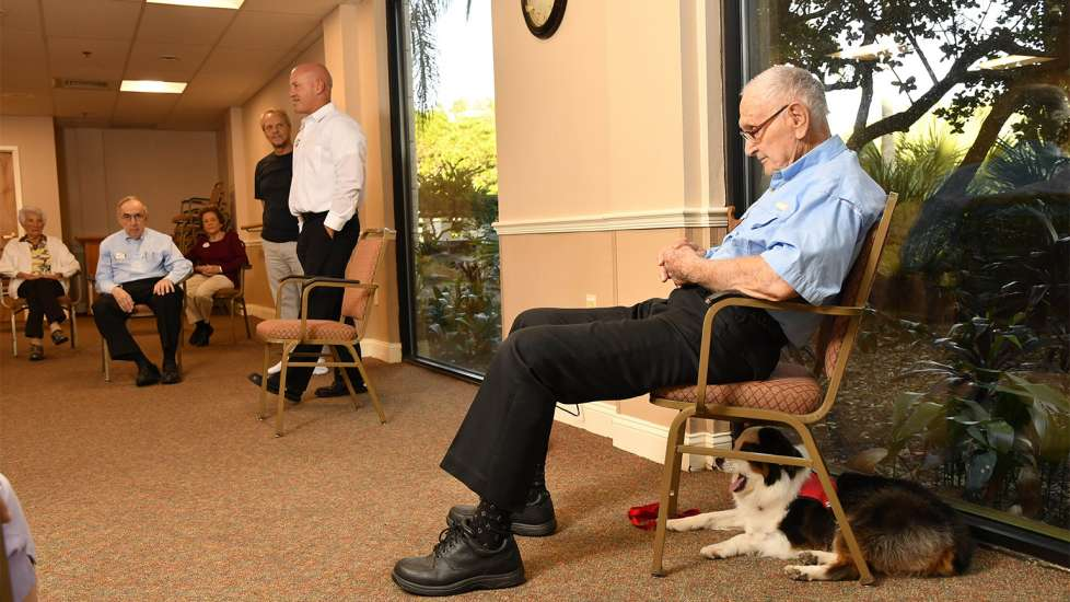 Jack and his handler, Roger Weiland, take a breather during a visit with a group of seniors participating in a Tai Chi class.