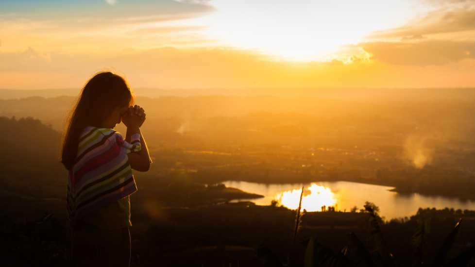 A young girl praying outdoors during a brilliant sunset.