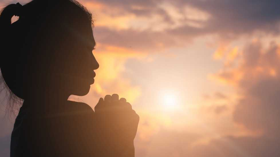 Silouette of a young woman in prayer.