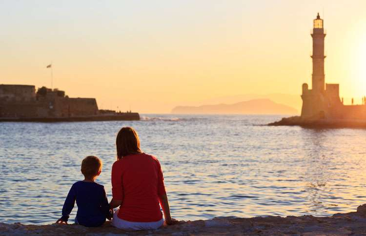 A mother and son sit on a beach at sunset and gaze at a lighthouse