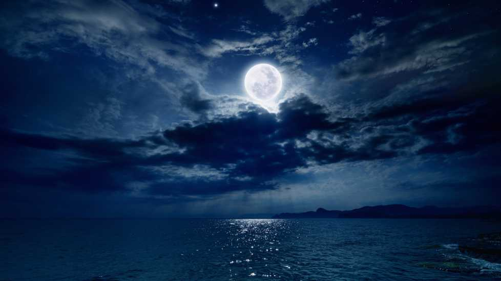 The night sky against the ocean with a full moon shining through dark clouds.